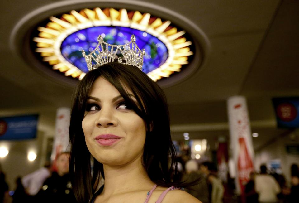 Miss Puerto Rico Collegiate Shaina Millan waits in the lobby of Boardwalk Hall before the Miss America 2014 pageant, Sunday, Sept. 15, 2013, in Atlantic City, N.J. (AP Photo/Julio Cortez)