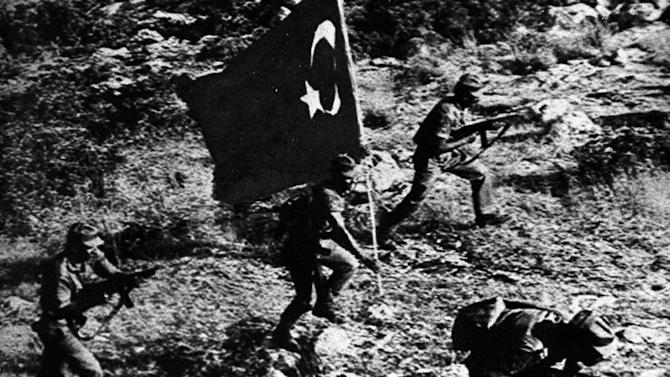 FILE- Carrying a Turkish flag, Turkish soldiers advance during the fighting that followed the July 20, 1974, Turkish invasion of Cyprus, in this file photo dated July 24, 1974, as Turkey seized nearly 40 percent of the island and even more of its economic potential. After the 1974 invasion the people of Cyprus were forced to rebuild their lives and their economy from scratch, not something they Cypriot people ever wanted to to again, but following the 2013 collapse of the financial industry and the international financial bailout, even the most sanguine forecaster predicts many years of recession and sky-high unemployment. (AP Photo, File)