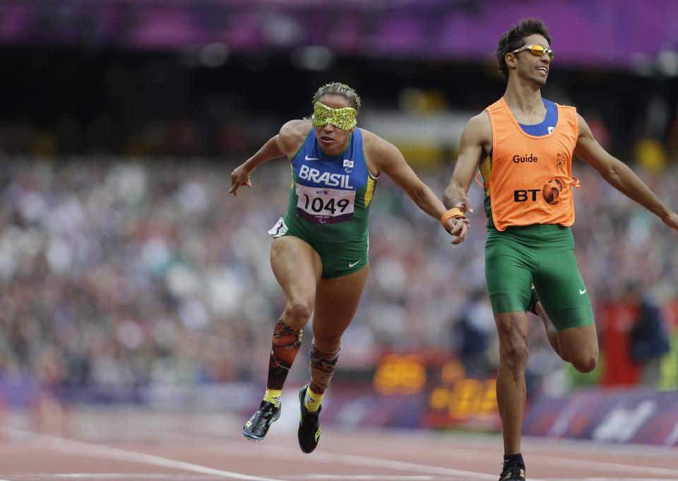 Brazil's Terezinha Guilhermina, along with her guide Guilherme Soares de Santana, competes during a women's 200m T11 round 1 race at the 2012 Paralympics in London, Saturday, Sept. 1, 2012. (AP Photo/Lefteris Pitarakis)