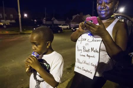 A woman looks at her phone as her son eats an ice-cream during a small demonstration protesting in the St. Louis area