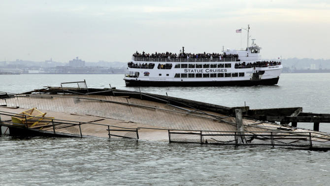 A Statue Cruises tour boat passes the damaged auxiliary pier on Liberty Island, in New York, Friday, Nov. 30, 2012. Tourists in New York will miss out for a while on one of the hallmarks of a visit to New York, seeing the Statue of Liberty up close. Though the statue itself survived Superstorm Sandy intact, damage to buildings and Liberty Island's power and heating systems means the island will remain closed for now, and authorities don't have an estimate on when it will reopen. (AP Photo/Richard Drew)