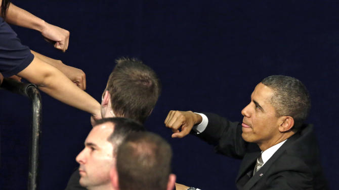 President Barack Obama acknowledges the crowd as he exchanges fist bumps with the audience after speaking at Hyde Park Academy, Thursday, Feb. 14, 2013, in Chicago. (AP Photo/M. Spencer Green)