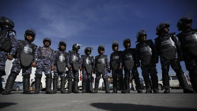 Nepalese riot police gather around the Constitution assembly members as they walk out shouting slogans after a meeting at the parliament in Kathmandu