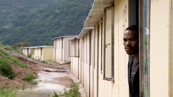** ADVANCE FOR SUNDAY NOV. 21** In this photo taken on Oct. 21, 2010, recovering addict Thamsanqa Langa looks out his door in the Kwadebeka Township near Durban, South Africa. Langa says he smoked whoonga, a concoction of AIDS drugs mixed with marijuana, for four years until he gave it up in March. Langa said he mooched AIDS drugs from HIV-infected friends, robbed houses, became a dealer and missed so many workdays that he lost his factory job. (AP Photo/John Robinson)