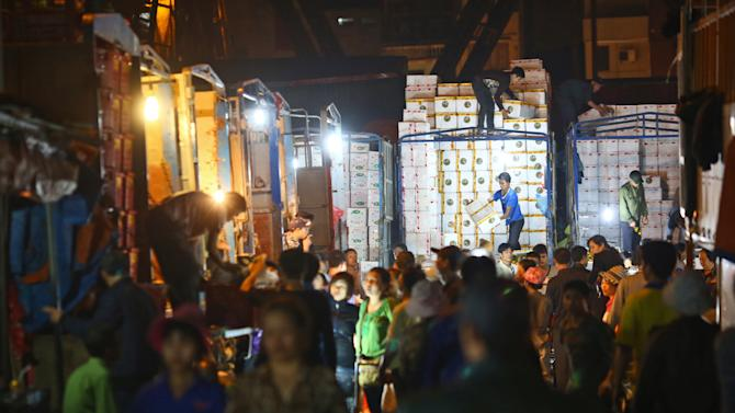 In this March 9, 2013 photo,  porters unload boxes of Chinese fruits near traders at work at Long Bien wholesale market for fruits and vegetables in Hanoi, Vietnam. Around half of the produce at the market is trucked in from China, arriving in the city in the middle of the night and distribute for Hanoi and neighbor areas. While fears about the safety of Chinese food products are often well founded, in Vietnam they are so tangled up with anti-Chinese sentiment it is hard to tell where one begins and the other ends. More than 1,000 years of occupation, a bloody border war in 1979 and renewed assertiveness by China in pushing territorial claims in the South China Sea mean that tales of Chinese perfidy find fertile soil in which to grow.(AP Photo/Na Son Nguyen)
