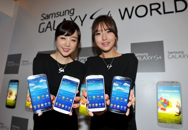 Samsung Electronics employees display the  Galaxy S4 smartphone in Seoul on April 25, 2013