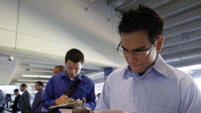 In this Wednesday, Oct. 24, 2012 photo, Fabio Magliano, right, fills out a job application as he stands in line at a job fair in Miami. According to government reports released Friday, Nov. 2, 2012, the U.S. economy added 171,000 jobs in October, and the unemployment rate ticked up to 7.9 percent. (AP Photo/Alan Diaz)