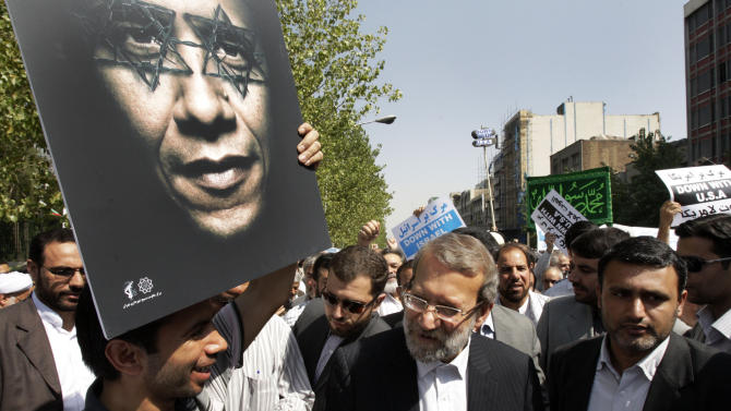 Iranian parliament speaker Ali Larijani, center, attends a protest after the Friday prayer, on Friday, Sept. 14, 2012, while a worshipper holds up a poster of US President Barack Obama, as part of widespread anger across the Muslim world about a film ridiculing Islam's Prophet Muhammad. (AP Photo/Vahid Salemi)