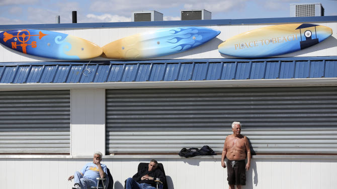 In a Saturday March 30, 2013, photo men sunbathe in front of a closed business on the boardwalk of New York's Coney Island.  Despite making the traditional Palm Sunday opening, many of the seasonal businesses at Coney Island are still reeling from the aftermath of Superstorm Sandy. (AP Photo/Mary Altaffer)