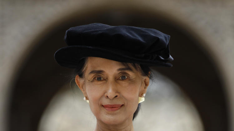"Myanmar opposition leader Aung San Suu Kyi, poses for the photographers following an award ceremony at the Oxford University, Oxford, England, on Wednesday, June 20, 2012.  It was a long wait, but Aung San Suu Kyi has finally received her honorary degree from Oxford University. In her speech, Suu Kyi praised the role Oxford played in helping her see humankind at its best during her long years under house arrest in Myanmar. ""The most important thing that I learned was respect for all of civilization,"" she said, wearing a traditional red gown. ""In Oxford I learned to respect all that is best in human civilization. That helped me cope with something that was not quite the best."" (AP Photo/Lefteris Pitarakis)"
