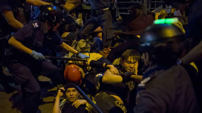 Pro-democracy protesters fall on the ground as they are chased by riot police at Mong Kok shopping district in Hong Kong