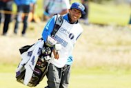 Manchester City's Carlos Tevez carries the bag of Andres Romero of Argentina on the 13th fairway at British Open Golf Championship at Royal Lytham and St Annes. Tevez made his debut as a pro caddy at the British Open on Sunday and judging by his player's score it may well be his finale as well