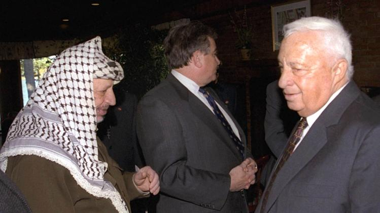"""FILE - In this Oct. 21, 1998 file photo, Israeli Foreign Minister Ariel Sharon, right, stands near but does not look at, or shake hands with, Palestinian leader Yasser Arafat at Wye Plantation, Maryland. Before becoming a candidate, Sharon proudly boasted he had never shaken hands with Arafat, and called the Palestinian leader a """"murderer and a liar"""" in an interview with the New Yorker magazine. Sharon, the hard-charging Israeli general and prime minister who was admired and hated for his battlefield exploits and ambitions to reshape the Middle East, died Saturday, Jan. 11, 2014. The 85-year-old Sharon had been in a coma since a debilitating stroke eight years ago. (AP Photo/Israel Government Press Office, File)"""