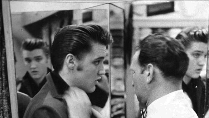 FILE - This 1956 file photo originally released courtesy of Bernard Lansky shows singer Elvis Presley, left, being outfitted by clothier Bernard Lansky at Lansky's Men's Store in Memphis, Tenn. Lansky, who helped a young Elvis Presley establish his signature clothing style, died Thursday, Nov. 15, 2012 at his Memphis home, according to his granddaughter Julie Lansky. He started his retail business in Memphis in 1946 with a $125 loan from his father, Samuel.  He was 85. (AP Photo/courtesy of Bernard Lansky, File)