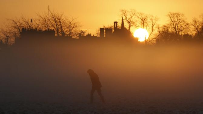 A person walks during sunrise in Knutsford