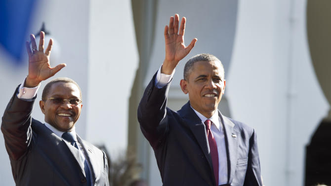 U.S. President Barack Obama, right, and Tanzanian President Jakaya Kikwete, left, wave as they enter State House, in Dar es Salaam, Tanzania Monday, July 1, 2013. Teeming crowds and blaring horns welcomed President Barack Obama to Tanzania's largest city, where the U.S. president's likeness is everywhere as he arrived on the last leg of his three-country tour of the African continent. (AP Photo/Ben Curtis)