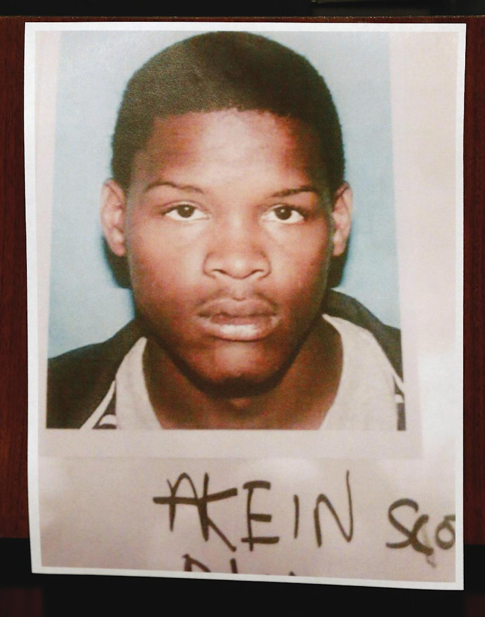 New Orleans Police Superintendent Ronal Serpas present a photo of 19-year-old Akien Scott who is wanted in the Mother's Day shootings during a news conference in front of police headquarters in New Orleans, Monday, May 13, 2013. (AP Photo/Bill Haber)