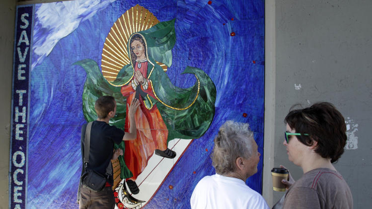 EDS: CORRECTS SPELLING OF CINCINNATI - In this May 27, 2011 photo, Jules Itzkoff, of Cincinnati, Ohio, left, looks at an image of the Virgin of Guadalupe riding a surfbaord that hangs under a train bridge as Starr Culver, right, and Mary Martin, center, both of Leucadia, Calif., embrace in Encinitas, Calif. The unauthorized artwork is drawing a mass following, and even city officials who say she must go say they too have been taken by her. (AP Photo/Gregory Bull)