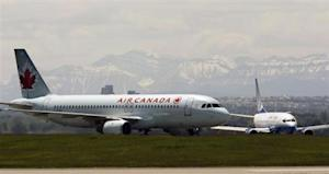 An Air Canada plane lands in front of a United plane at the Calgary International Airport