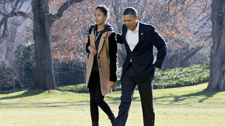 President Barack Obama walks with daughter Malia on the first family's return from vacationing in Hawaii, on the South Lawn of the White House in Washington, Sunday, Jan. 6, 2013. (AP Photo/Jacquelyn Martin)