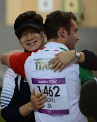 South Korean Jin Jong-Oh (L) hugs Italian Luca Tesconi after he won the 10m air pistol men final at the Royal Artillery Barracks in London