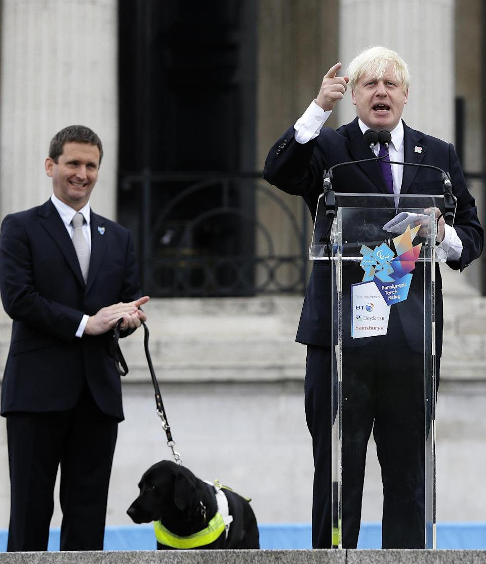 Boris Johnson, The Mayor of London, watched by Chris Holmes, Director of Paralympic Integration, and his dog Lottie, makes a speech ahead of the lighting of the Paralympic flame cauldron in Trafalgar Square in London, Friday, Aug. 24, 2012. (AP Photo/Kirsty Wigglesworth)
