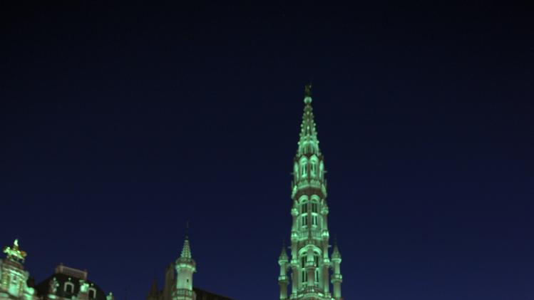 Irish tourists look at the Brussels Grand Place lit in green on the occasion of St. Patrick's Day in Brussels