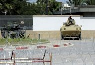 Tunisian soldiers guard the US embassy building in Tunis. Al-Qaeda called for fresh attacks against US targets in the Arab world and the West, as Washington said it was pulling non-essential embassy staff out of Sudan and Tunisia