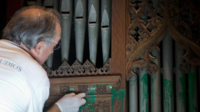 William Adair of Gold Leaf Studios remove green paint from the organ in the Washington National Cathedral's historic Bethlehem Chapel, Tuesday, July 30, 2013, in Washington. Officials at the cathedral discovered the paint inside two chapels Monday afternoon. The paint was splashed onto the organ and on the floor inside the Bethlehem Chapel on the basement level and inside Children's Chapel in the nave of the cathedral. (AP Photo/Carolyn Kaster)