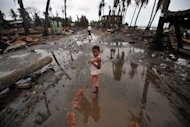 "A child stands in a street lined with destroyed buildings following days of sectarian violence in Sittwe, capital of Myanmar's western state of Rakhine on June 16. Fresh communal violence has left at least three people dead in western Myanmar, government officials said Wednesday, as the United States praised Naypyidaw's ""constructive"" response to the clashes"