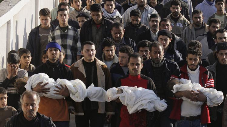 FILE - In this Monday, Jan. 5, 2009 file photo Palestinians carry the bodies of three toddlers Ahmed, Mohamed, and Issa Samouni, who according to Palestinian medical sources were killed in an Israeli strike, during their funeral in Gaza City. The Israeli military has decided on Tuesday, May 1, 2012 not to file any charges in one of the gravest incidents in its 2009 war in the Gaza Strip, closing its investigation in the shelling deaths of 21 members of a single Palestinian family without holding anyone responsible. (AP Photo/Hatem Moussa, File)
