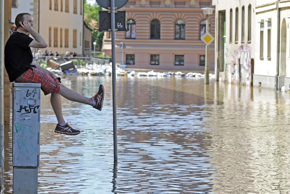 A man talks on his cellphone as he sits on a power distribution station in an area flooded by river Saale in Halle, central Germany, Wednesday, June 5, 2013. Heavy rainfalls cause flooding along rivers and lakes in Germany, Austria, Switzerland, the Czech Republic and Hungary. (AP Photo/Jens Meyer)
