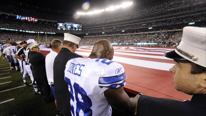 Dallas Cowboys running back Felix Jones (28) holds an American flag with first responders during the national anthem before an NFL football game between the Dallas Cowboys and New York Jets, Sunday, Sept. 11, 2011,  in East Rutherford, N.J. (AP Photo/Henny Ray Abrams)