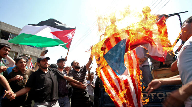 Demonstrators burn a U.S. flag as a Jordanian flag is held aloft by a protester in Amman, Jordan, Friday July 22, 2011. Protesters denounce what they call U.S. interference in their government's policies, demanded democratic reforms sweeping the Arab region, and for Prime Minister Marouf al-Bakhit to step down. Jordan's King Abdullah II is a staunch U.S. ally. (AP Photo/Mohammad Hannon)
