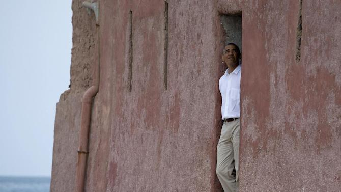 "President Barack Obama looks out of the ""door of no return"" during a tour of Goree Island, Thursday, June 27, 2013, in Goree Island, Senegal. Goree Island is the site of the former slave house and embarkation point built by the Dutch in 1776, from which slaves were brought to the Americas. The ""door of no return"" was the entrance to the slave ships. (AP Photo/Evan Vucci)"