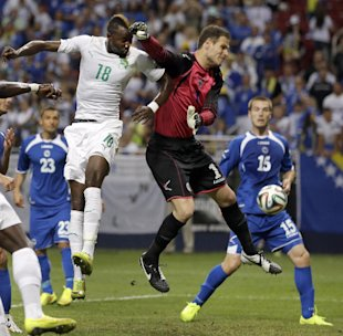 Bosnia goalkeeper Asmir Begovic, center, deflects a head ball away from Ivory Coast's Lacina Traore (18) as Bosnia's Toni Sunjic (15) watches during t...