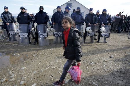 A Syrian refugee girl walks by Greek police before crossing the border from Greece to Macedonia near the Greek village of Idomeni