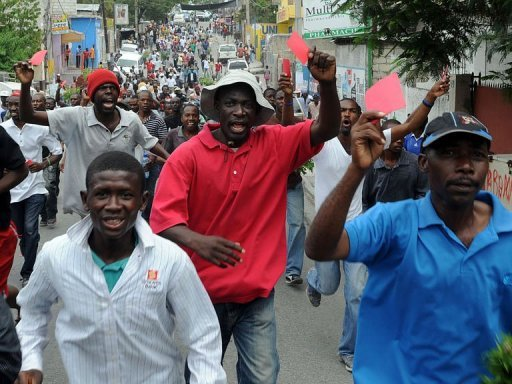 <p>Haitians protest against the government and the cost of living on September 30, 2012 in Port-au-Prince. The demonstrators hold red cards demanding the departure of Haitian President Michel Martelly.</p>
