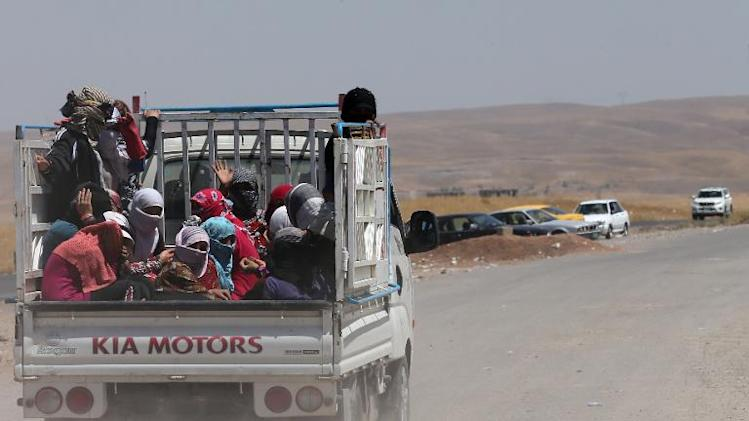 Iraqi families arrive at a temporary camp set up to house civilians fleeing violence, in Aski kalak on June 15, 2014