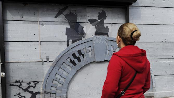 """A woman looks at work by British graffiti artist Banksy on Saturday, Oct. 19, 2013 in the Brooklyn borough of New York. The building owner has hired security guards and installed a metal gate to protect a work by Banksy. Cara Tabachnick, whose family owns the building, said the goal is to preserve the artwork """"so it can be viewed and enjoyed."""" Most of the Banksy works that have gone up have been tagged over by others, and some have been completely erased. Mayor Michael Bloomberg said last week that graffiti ruins property and is """"a sign of decay."""" (AP Photo/Alyssa Goodman)"""
