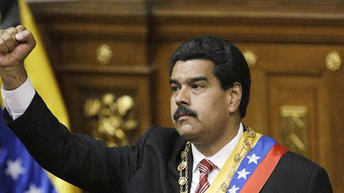 Nicolas Maduro raises his fist as he dons the presidential sash after he was sworn in as Venezuela's president at the National Assembly in Caracas, Venezuela, Friday, March 8, 2013. Maduro was sworn in Friday as Venezuela's acting president, against the objections of the political opposition who said the move violated the country's constitution.  Late President Hugo Chavez designated Vice President Maduro as his successor before he died Tuesday of cancer.  (AP Photo/Fernando Llano)