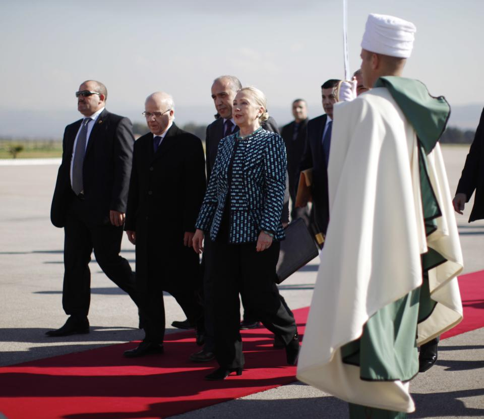 U.S. Secretary of State Hillary Rodham Clinton, centre, walks with Algerian Foreign Minister Mourad Medelci, 2nd left, upon her arrival in Algiers, Saturday Feb. 25, 2012.  (AP Photo/Jason Reed, Pool)