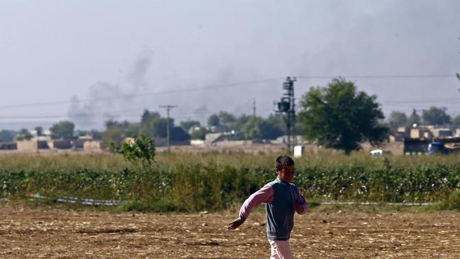 A boy plays soccer as smoke rises over the Syrian town of Kobani near the Mursitpinar border crossing, on the Turkish-Syrian border in the southeastern town of Suruc