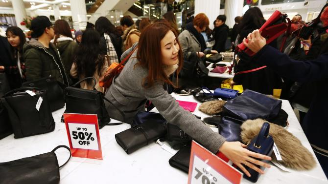 A shopper reaches for a handbag as she hunts for bargains at Selfridges department store on the first day of their sales, in central London