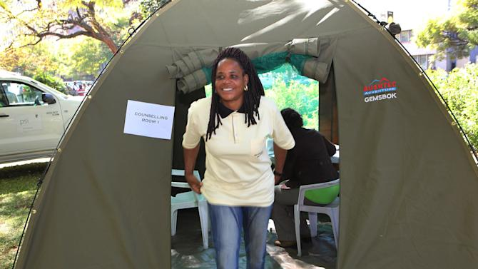 """Evelyn Masaiti, a member of parliament in Zimbabwe, emerges out of a tent after she was tested for HIV and Aids in Harare, Friday, June, 22, 2012. In Zimbabwe's parliament, lawmakers belonging to a panel on health issues are setting up an HIV/AIDS testing and male circumcision center. Lawmaker Blessing Chibundo of the Zimbabwe prime minister's party said Friday the campaign, the first of its kind involving the country's leaders, is a show of """"political will"""" to fight AIDS.(AP Photo/Tsvangirayi Mukwazhi)"""