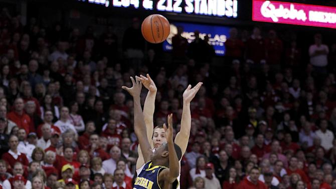 Wisconsin's Ben Brust, top, shoots a 3-point basket against Michigan's Caris LeVert in the final second of regulation to tie the NCAA college basketball game Saturday, Feb. 9, 2013, in Madison, Wis. Wisconsin defeated Michigan 65-62. (AP Photo/Andy Manis)