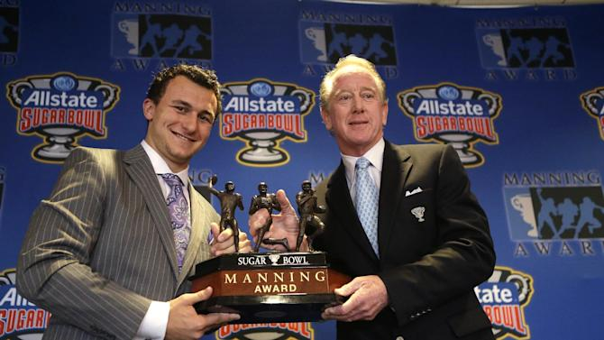 Heisman Trophy winner and Texas A&M quarterback Johnny Manziel, left, poses with former NFL quarterback Archie Manning and the the Manning Award, which Manziel will be receiving as the nation's top quarterback, Thursday, May 2, 2013, in New Orleans. (AP Photo/Gerald Herbert)
