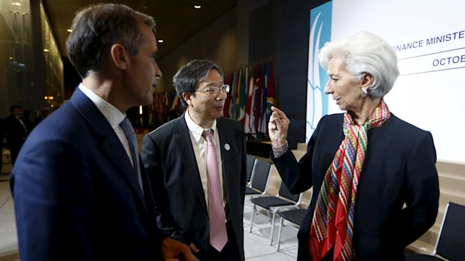 Jens Weidmann, Yi Gang and Christine Lagarde talk after a G-20 group family picture at the 2015 IMF/World Bank Annual Meetings in Lima