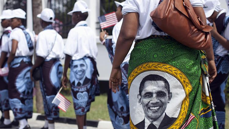 Young girls and women wear khangas, a traditional wrap, with the image of U.S. President Barack Obama as they line up to enter the State House, in Dar es Salaam, Tanzania, Monday, July 1, 2013, to greet and perform for U.S. President Barack Obama and first lady Michelle Obama. The Democratic president is due to fly into Dar es Salaam, Tanzania on Monday, the last stop on a weeklong tour of Africa that wraps up Tuesday, while his Republican predecessor coincidentally also plans to be there for a conference on African women organized by the George W. Bush Institute. (AP Photo/Carolyn Kaster)