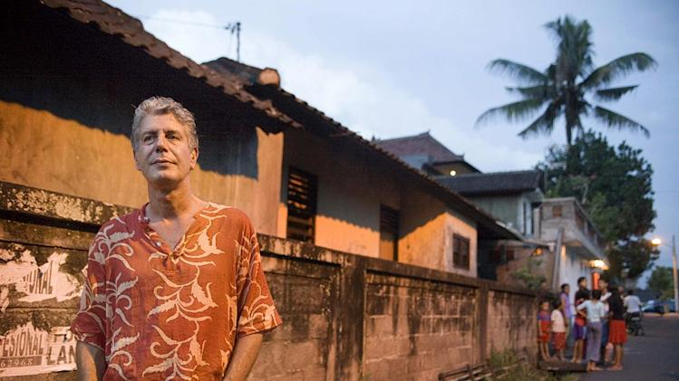 Anthony Bourdain stands near a wall and some buildings and a cluster of people appears in the background as seen on Anthony Bourdain: No Reservations.